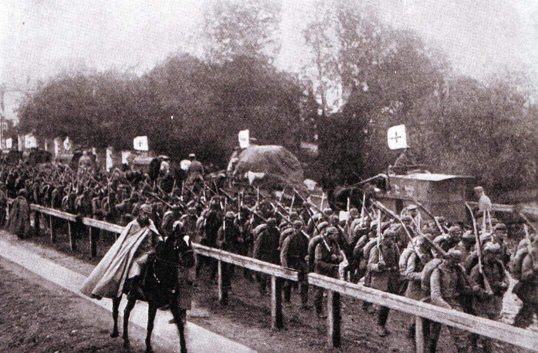 Advancing German infantry pass a Red Cross column