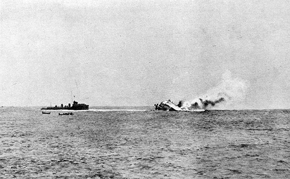 The German light cruiser SMS Mainz sinking during the Battle of Heligoland Bight on 28th August 1914. The ship on the left is HMS Lurcher taking off German survivors. The boats are from HMS Liverpool.