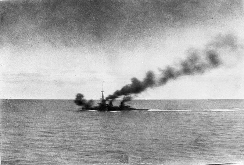HMS Inflexible opens fire on SMS Gneisenau during the Battle of the Falkland Islands on 8th December 1914. Photograph taken by Paymaster Sub-Lieutenant Duckworth RN from HMS Invincible. Smoke from HMS Invincible can be seen at the top of the photograph