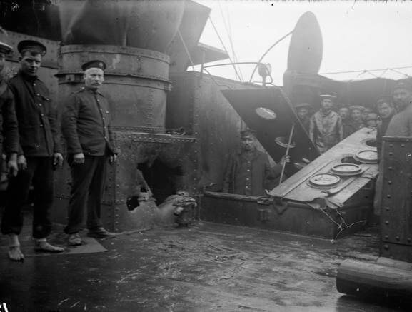 Shell hole in a casemate on HMS Kent made during the Battle of the Falkland Islands on 8th December 1914. Sergeant Mayes RMA stands to the left of the hole
