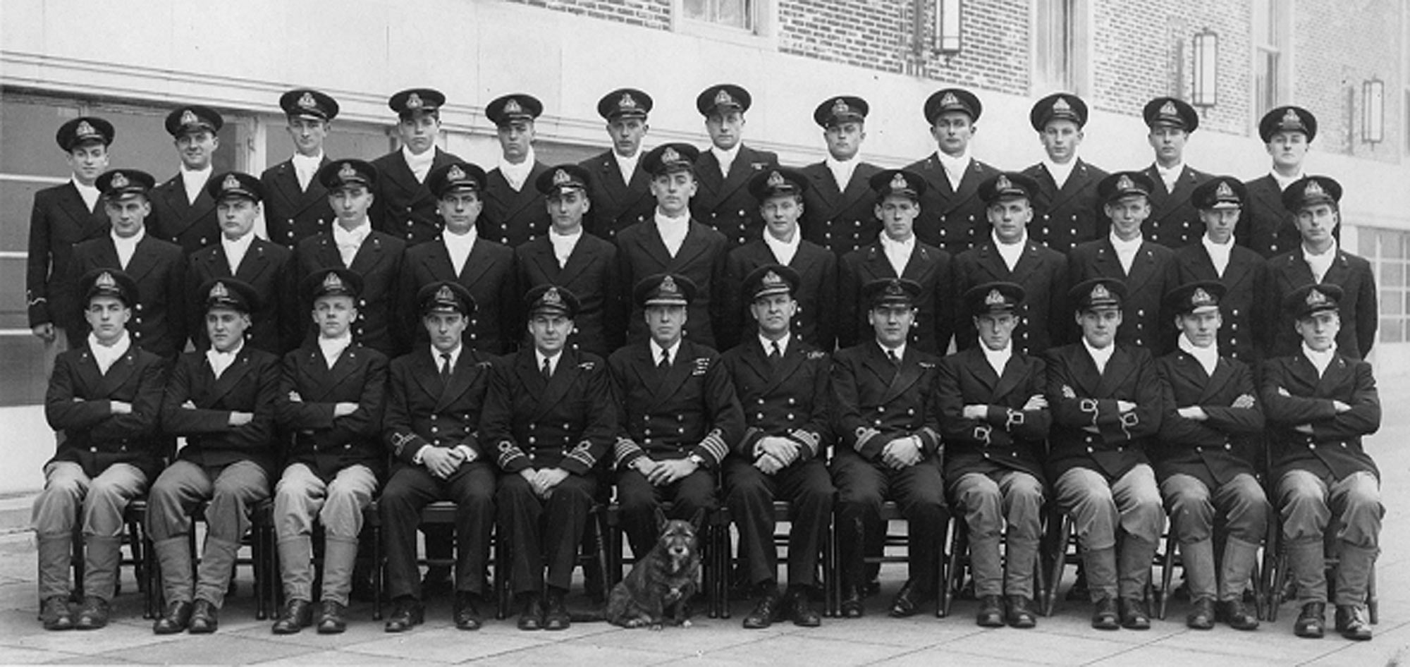 Captain Cuthbert Coppinger DSC RN the commanding officer of HMS King Alfred, the RNVR training station, in the middle of the front row with his dog training staff and trainees in 1945