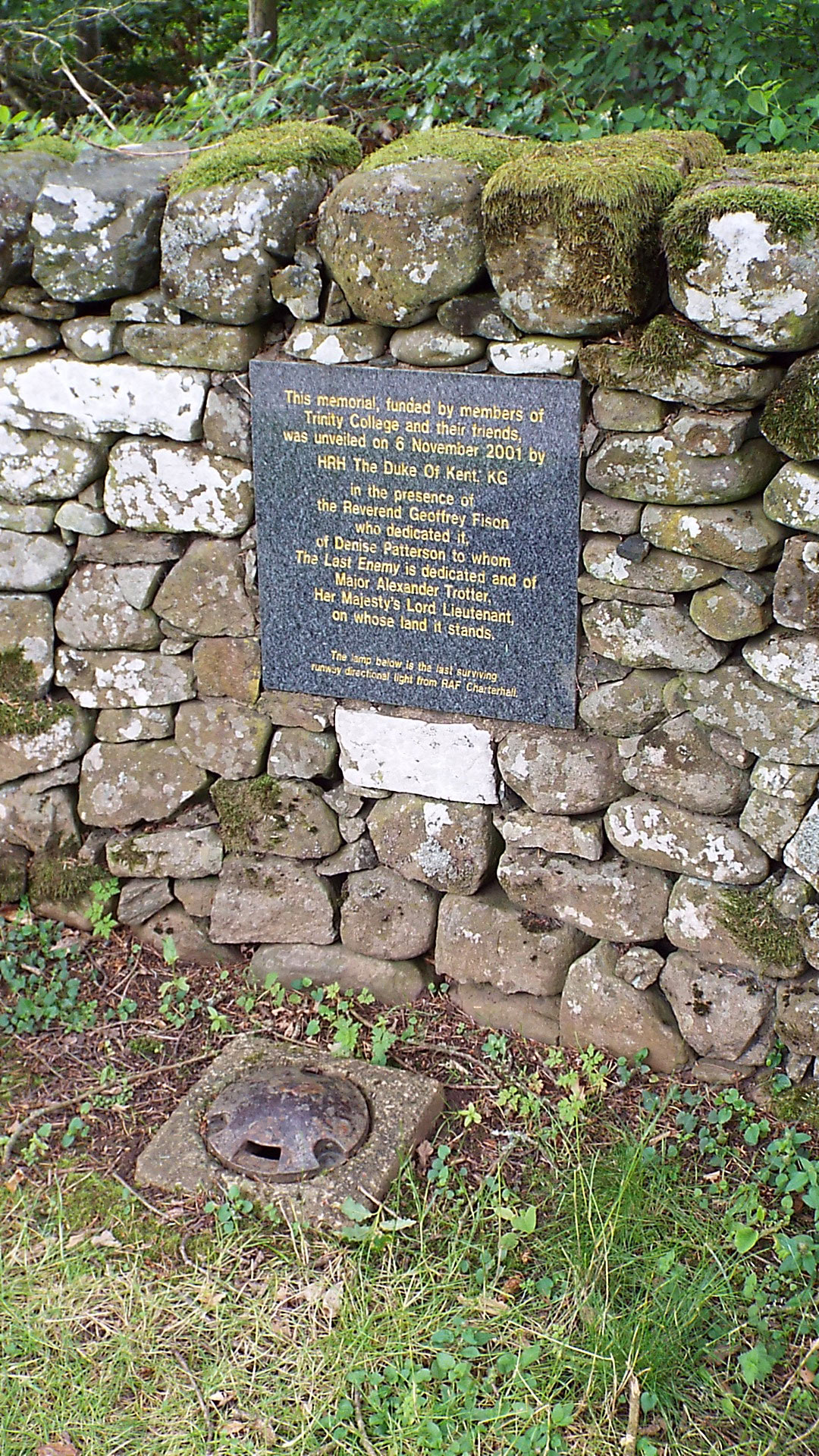 The Plaque behind the Memorial to Richard Hilary. Beneath the Plaque is a runway light from RAF Charterhall