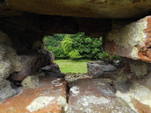 View through the sole remaining musket loop-hole in the western perimeter wall of Basing House overlooking Slaughter Close: Siege of Basing House 1642 to 1645 during the English Civil War