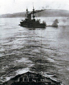 HMS Albion, pre-Dreadnought British battleship, aground in the Dardanelles during the bombardment of the Turkish land defences and being towed off by HMS Canopus