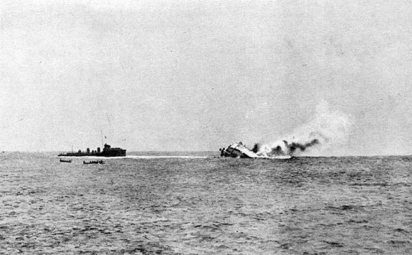 German light cruiser SMS Mainz sinking during the Battle of Heligoland Bight on 28th August 1914 in the First World War. The ship on the left is HMS Lurcher taking off German survivors. The boats are from HMS Liverpool