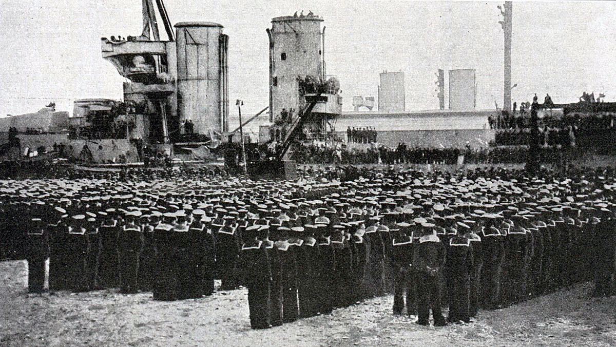 King George V addressing a parade of sailors from the Grand Fleet after the Battle of Jutland speaking from the deck of the badly damaged HMS Warspite